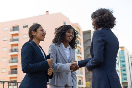 Photo pour Multiethnic partners greeting each other near office building. Business women shaking hands with each other outside in city. Partnership concept - image libre de droit
