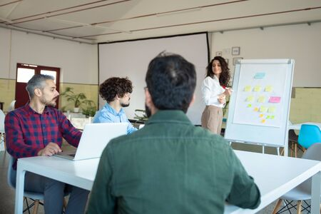 Foto de Smiling young woman explaining strategy to coworkers. Confident businesswoman standing near board with flowchart made from sticky notes. Business strategy concept - Imagen libre de derechos