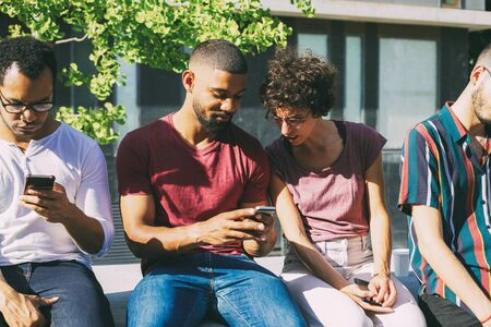 Photo pour Cheerful handsome man showing phone screen to disgusted woman. People with smartphones sitting on parapet outdoors. Wireless connection concept - image libre de droit
