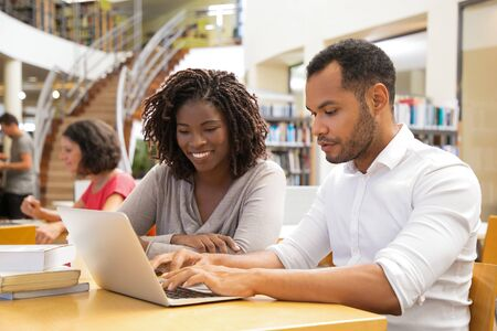 Photo pour Cheerful young people working with laptop at library. Two joyful students working together. Education concept - image libre de droit