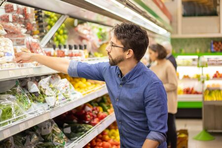 Foto für Young man shopping in grocery store. Side view of focused man and woman holding shopping baskets and choosing fresh fruits and vegetables in supermarket. Shopping concept - Lizenzfreies Bild