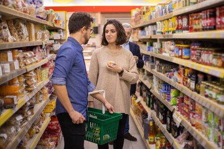 Foto für Couple shopping together in grocery store. Young man and woman with shopping basket choosing goods together in supermarket. Shopping concept - Lizenzfreies Bild