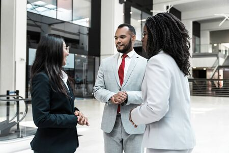 Photo pour Agent and clients meeting and discussing deal in office hall. Business man and women standing in hallway and talking. Negotiation or dealing concept - image libre de droit