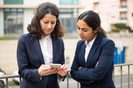 Photo for Serious businesswomen using smartphone. Female colleagues in formal wear standing on street and using cell phone together. Business and technology concept - Royalty Free Image