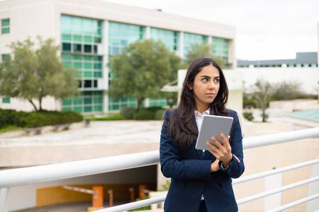 Photo pour Serious young woman with tablet pc. Focused young businesswoman holding digital tablet and looking aside in urban city. Wireless technology concept - image libre de droit