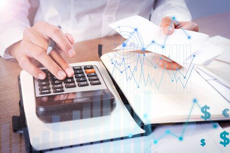 Photo for Person calculating on calculator with financial analysis graphs. Notebook and calculator lying on desk. Accountancy concept. Cropped view. - Royalty Free Image