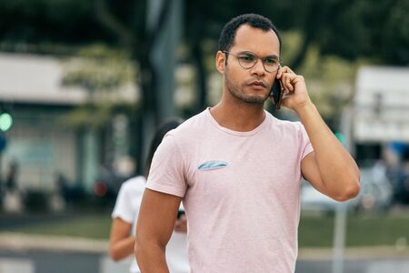 Foto de Handsome serious man talking on phone while walking on street. Front view of focused young guy having conversation through smartphone. Communication and technology concept - Imagen libre de derechos