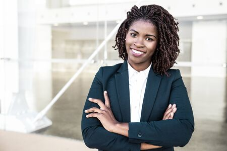 Photo for Happy successful professional posing near office building. Young African American business woman with arms folded standing outside, looking at camera, smiling. Female business leader concept - Royalty Free Image