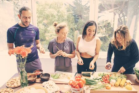 Photo for Cheerful friends preparing healthy meal. Happy young man and women in sportswear standing at table with raw organic fruits and vegetables. Healthy eating concept - Royalty Free Image
