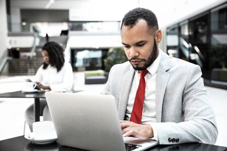 Photo pour Focused serious professional using laptop while drinking coffee in office lobby. Young African American woman using tablet in background. Wireless technology concept - image libre de droit