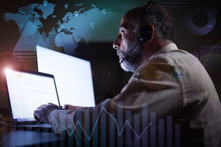 Foto de Man in headset using laptop and virtual statistic graphics. Side view of focused mature male call center operator in headset working with computer in dark office. Customer support concept - Imagen libre de derechos