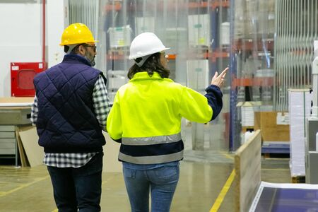 Photo pour Back view of employees walking at factory and pointing to right. Rear view of confident machine operators looking aside. Print manufacturing concept - image libre de droit