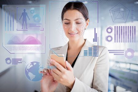Photo pour Closeup portrait of smiling beautiful young business woman wearing jacket and using smartphone in office hall. Communication concept with face scan virtual infographics - image libre de droit