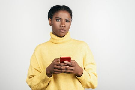 Photo pour Serious African American woman holding smartphone. Front view of concentrated young lady using phone. Technology concept - image libre de droit