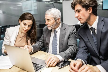 Photo pour Confident business team looking at laptop. Group of office employees sitting at table and discussing new project. Business, teamwork concept - image libre de droit