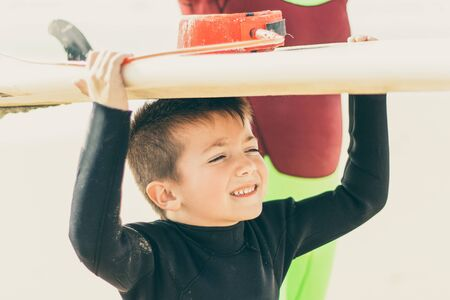 Photo pour Cute little boy holding surfboard. Adorable smiling child in wetsuit holding surfboard and looking aside on sandy beach. Surfing concept - image libre de droit