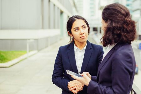 Foto de Businesswoman using smartphone and looking at colleagues. Female colleagues in formal wear standing on street with mobile phone and looking at each other. Communication concept - Imagen libre de derechos