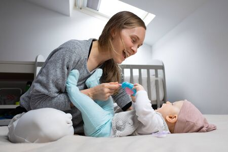 Foto für Joyful mom entertaining baby with rattle toy, having fun with daughter in bedroom. Mother and little child staying at home. Child care or isolation concept - Lizenzfreies Bild