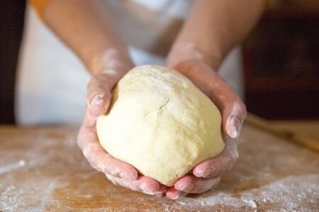 Foto für Unrecognizable baker holding kneaded dough in palms. Wheat flour on wooden board. Selective focus. Studio shot. Front view. Cooking and baking at home concept - Lizenzfreies Bild