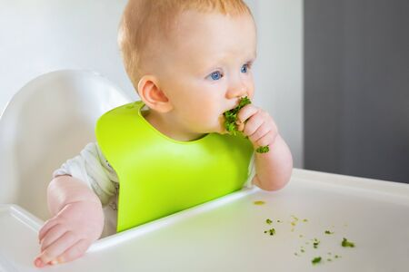 Photo pour Cute red haired baby eating broccoli, sitting in highchair. Little child wearing plastic bib having dinner with green vegetables. Closeup shot. First solid food or child care at home concept - image libre de droit