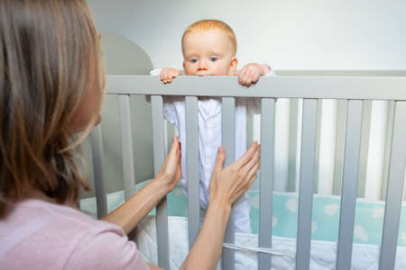 Mother training baby to stand in crib, holding and supporting child. Toddler standing in crib and holding railing. Child care or childhood concept