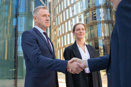 Photo pour Confident businessmen shaking hands outdoors. Men and woman wearing office suits standing among city buildings and discussing contract. Agreement and partnership concept - image libre de droit
