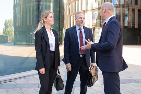 Foto de Confident professional adult businesspeople meeting outdoors. Content business man and woman in suit listening boss and smiling. Teamwork, negotiation and partnership concept - Imagen libre de derechos