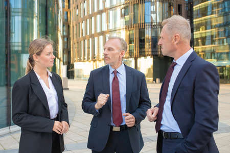 Photo for Focused business colleagues wearing office suits, meeting outdoors, standing and talking with city buildings in background. Corporate communication concept - Royalty Free Image