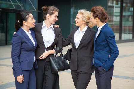 Photo for Happy businesswomen celebrating team success, standing outdoors, hugging and talking. Team support and congratulation concept - Royalty Free Image