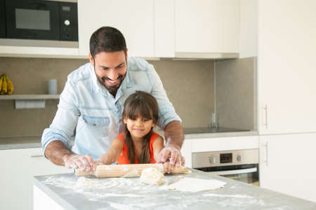 Photo for Cheerful Latin girl and her dad rolling and kneading dough on kitchen table with flour powder. Father helping daughter to bake bread or pies. Home activities concept - Royalty Free Image