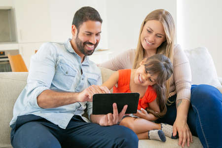 Photo pour Happy parents and cheerful girl sitting on couch, using tablet, watching movie or funny videos, laughing and having fun. Medium shot. Internet and communication concept - image libre de droit