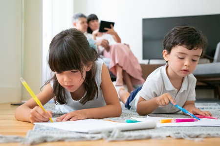Photo for Focused little boy and girl lying on floor and drawing in living room while parents sitting together in background. Childhood or children creative development concept - Royalty Free Image