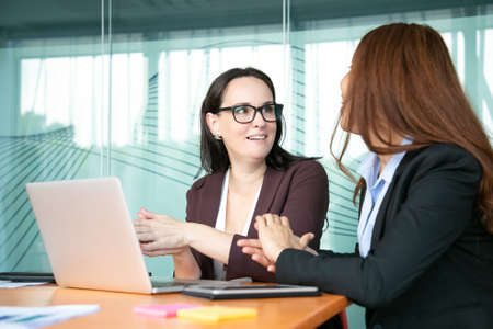 Photo pour Excited cheerful businesswomen discussing project while sitting at open laptop, talking and smiling. Business communication and teamwork concept - image libre de droit