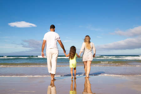 Photo pour Man, woman and kid wearing pale summer clothes, walking on wet sand to sea, spending leisure time on beach. Rear view. Family outdoor activities concept - image libre de droit