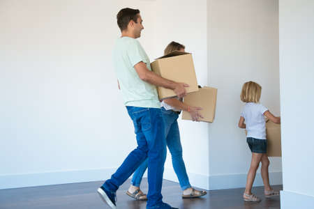 Photo for Father holding cardboard box and going to corridor after wife and daughter. Cheerful young family with kid relocating in new house or apartment together. Mortgage, relocation and moving day concept - Royalty Free Image