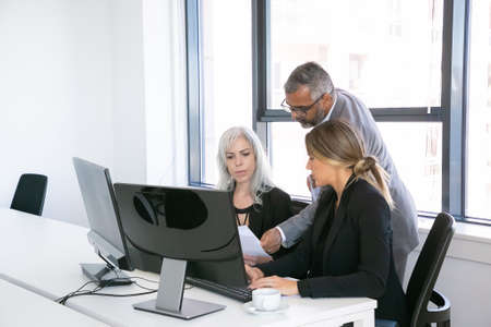 Photo pour Serious business group of three analyzing reports, sitting at workplace with monitors together, holding, reviewing and discussing papers. Copy space. Business meeting concept - image libre de droit