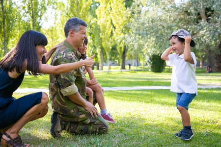 Photo for Happy military father in uniform returning to family. Children with mom meeting dad, boy trying on camouflage cap. Family reunion or returning home concept - Royalty Free Image