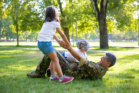 Photo pour Happy kids and their military dad lying and playing on grass in park. Girl pulling fathers hand. Family reunion or returning home concept - image libre de droit