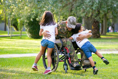 Photo pour Happy disabled military man in wheelchair returning home and hugging kids. Veteran of war or family reunion concept - image libre de droit