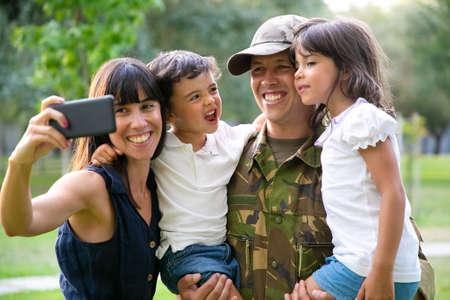 Photo pour Happy joyful military family celebrating dads returning, enjoying leisure time in park, taking selfie on smartphone. Medium shot. Family reunion or returning home concept - image libre de droit