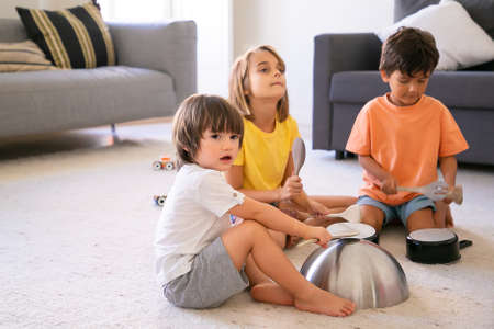 Photo pour Happy children sitting on carpet and playing with utensils. Cute Caucasian little boys and blonde girl having fun together in living room and knocking on pans. Childhood and home activity concept - image libre de droit
