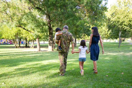 Photo for Back view of happy family walking together on meadow in park. Father wearing camouflage uniform, holding son and enjoying weekend with wife and kids. Family reunion and returning home concept - Royalty Free Image