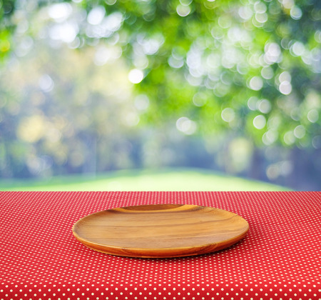 Empty round wooden tray on red polka dot tablecloth over blur trees with bokeh background, Product display montage