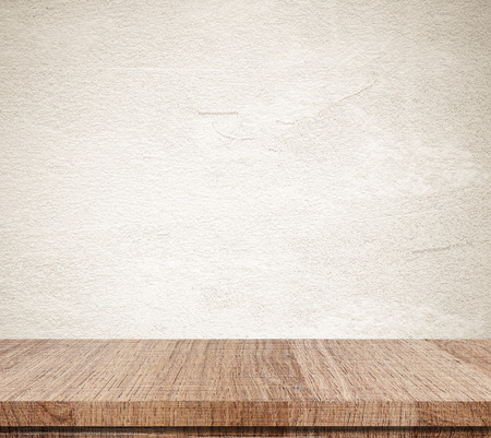 Empty wooden table over grunge cement wall