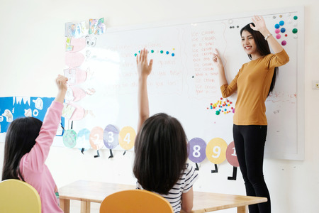 Foto de Young woman teacher teaching kids in kindergarten classroom - Imagen libre de derechos