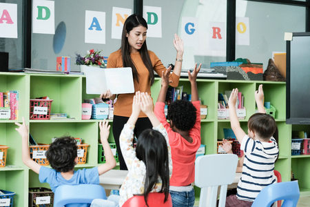 Foto de Young asian woman teacher teaching kids in kindergarten classroom, preschool education concept - Imagen libre de derechos