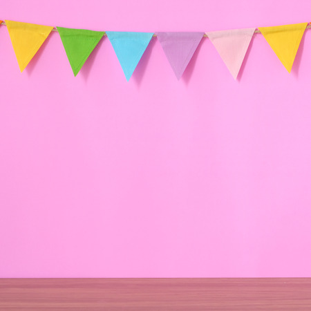 Colorful party flags hanging on pink background and wooden table, birthday, anniversary, celebrate event, festival greeting card background