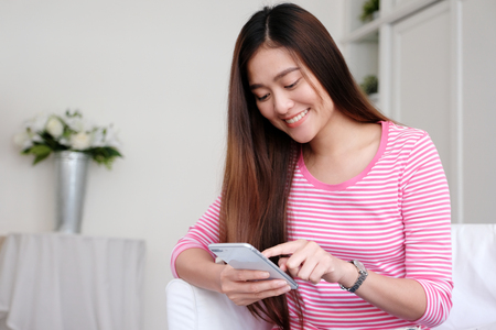 Photo pour Young asian woman using smart phone with smiling, happy and relax emotion in white room background, people on phone, lifestyle - image libre de droit