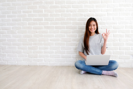 Photo for Young asian woman showing ok hand sign and smiling while working with laptop computer in white room with copy spce, people with positive gesture - Royalty Free Image
