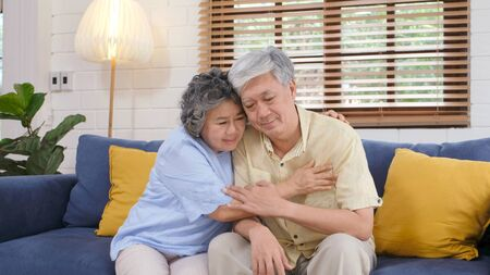 Foto de Senior asian couple comforting each other from depressed emotion while sitting on sofa at home living room, old retirement lifestyle - Imagen libre de derechos